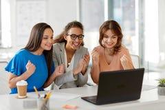 Счастливые коммерсантки с компьтер-книжкой на офисе Стоковая Фотография
