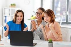 Счастливые коммерсантки с компьтер-книжкой на офисе Стоковое фото RF