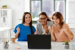 Счастливые коммерсантки с компьтер-книжкой на офисе Стоковые Фото