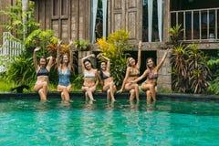 счастливые красивые девушки в swimwear сидя на бассейне и усмехаться стоковое фото rf