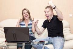Счастливые кричащие пожененные пары смотря в экране компьтер-книжки и показывать с оружиями, отечественной комнатой стоковое фото
