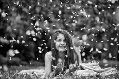 Счастливые лепестки ребенка и цветка Маленькая девочка на зеленой траве с лепестками стоковое фото