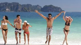 Счастливые люди бежать от воды держа руки на красивых друзьях группы пляжа, человека и женщины на каникулах моря видеоматериал