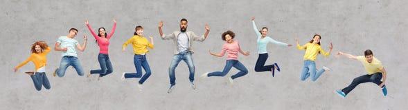Счастливые люди или друзья скача в воздух над серым цветом Стоковая Фотография