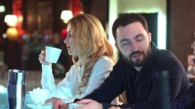 Счастливые люди общаясь и злословя над напитками в расслабленной окружающей среде в баре сток-видео