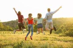 Счастливые люди скача в глушь Располагаясь лагерем сезон стоковые изображения rf