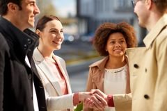 Счастливые люди тряся руки на улице города стоковое фото