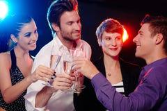 Счастливые люди clinking с шампанским Стоковая Фотография