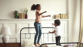 Счастливые маленькие африканские дети мальчик и девушка скача на кровать видеоматериал