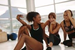 Счастливые маленькие девочки принимая selfie в спортзале Стоковое фото RF