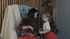 Счастливые маленькие ребеята - брюнет и блондинка и их очаровательная мать имеют потеху на Рожденственской ночи семья счастливая сток-видео