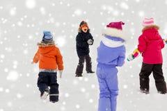 Счастливые маленькие ребеята играя outdoors в зиме стоковое изображение