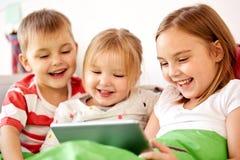 Счастливые маленькие ребеята с ПК таблетки в кровати дома Стоковое Изображение