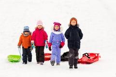 Счастливые маленькие ребеята с скелетонами в зиме стоковое фото rf