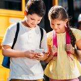 счастливые маленькие ученые используя смартфон совместно перед стоковое изображение rf