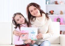 Счастливые мама и дочь показывают изображение для папы Фото с космосом экземпляра стоковые изображения