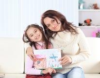 Счастливые мама и дочь показывают изображение для папы Фото с космосом экземпляра стоковая фотография