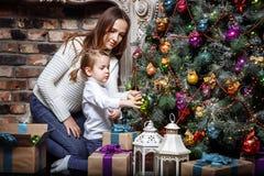 Счастливые мама и дочь семьи украшают рождественскую елку дома Стоковые Фото