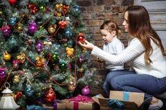 Счастливые мама и дочь семьи украшают рождественскую елку дома Стоковые Изображения RF