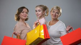 Счастливые мать, дочь и бабушка держа хозяйственные сумки, женский отд сток-видео