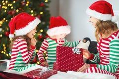 Счастливые мать и дети семьи в пижамах раскрывая подарки на chr стоковые изображения