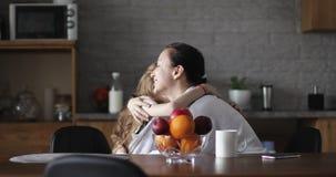 Счастливые мать и дочь сидят в кухне на таблице и иметь говорить потехи акции видеоматериалы