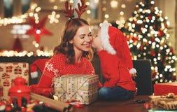 Счастливые мать и ребенок семьи пакуют подарки рождества стоковые изображения