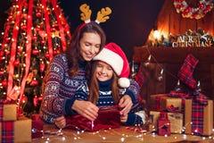 Счастливые мать и ребенок семьи пакуют подарки рождества стоковая фотография rf