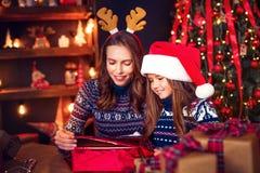 Счастливые мать и ребенок семьи пакуют подарки рождества стоковые изображения rf