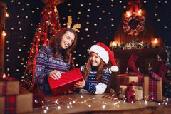 Счастливые мать и ребенок семьи пакуют подарки рождества стоковые фото