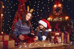 Счастливые мать и ребенок семьи пакуют подарки рождества стоковое изображение rf