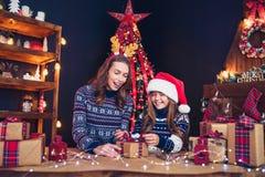 Счастливые мать и ребенок семьи пакуют подарки рождества стоковое изображение