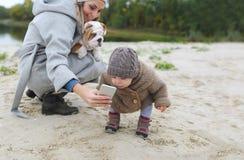 Счастливые мать и ребёнок при ее щенок делая selfie outdoors Стоковые Изображения RF