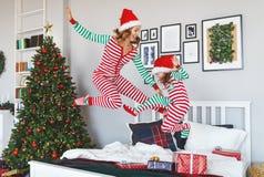 Счастливые мать семьи и дочь ребенка в пижамах скача в кровать дальше на утре рождества стоковые изображения rf