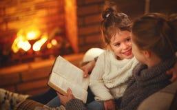 Счастливые мать семьи и дочь ребенка прочитали книгу на eveni зимы Стоковая Фотография