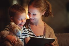счастливые мать семьи и сын ребенка с планшетом в вечере стоковые изображения rf