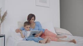 Счастливые мать семьи и сын ребенка с планшетом в вечере Счастливые мать семьи и сын ребенка с планшетом в вечере акции видеоматериалы
