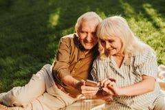 Счастливые мельком взглядывая серые с волосами пары используя сподручное стоковая фотография