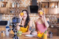 Счастливые милые женщины держа половины апельсина Стоковое Изображение RF
