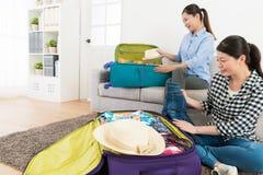 Счастливые милые сестры организуя одежду для того чтобы путешествовать стоковые фото