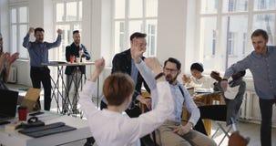 Счастливые многонациональные бизнесмены потехи празднуя успех вместе с возбужденный мужской хлопать стула офиса катания босса сток-видео