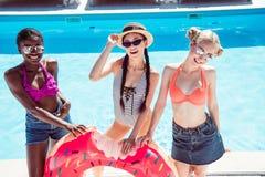 Счастливые многонациональные женщины представляя с раздувным донутом около бассейна стоковое фото