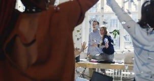 Счастливые многонациональные коллеги празднуют успех вместе с confetti, молодым женским стулом офиса катания босса компании акции видеоматериалы