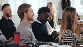 Счастливые многонациональные мужские коммерческие директоры сидят и слушают к семинару на современном конференции офиса Здоровое  сток-видео