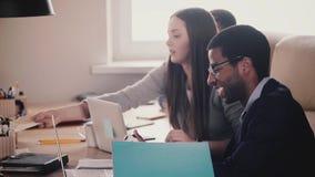 Счастливые многонациональные тысячелетние бизнесмены работают совместно таблицей в офисе современной светлой просторной квартиры  акции видеоматериалы
