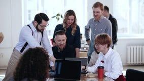 Счастливые многонациональные усмехаясь коллеги работают совместно, обсуждают проект на офисе просторной квартиры коллективно обсу сток-видео