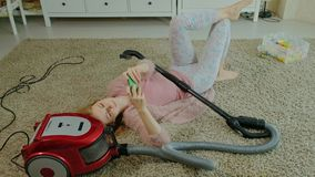 Счастливые молодая женщина или домохозяйка с пылесосом, лежа на полу-наушниках, пользы телефон, слушают музыку акции видеоматериалы