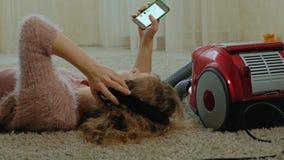 Счастливые молодая женщина или домохозяйка с пылесосом, лежа на полу-наушниках, пользы телефон, слушают музыку видеоматериал
