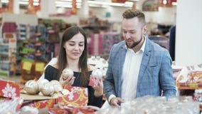 Счастливые молодой человек и женщина выбирают украшения рождества в магазине акции видеоматериалы