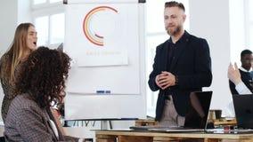 Счастливые молодые бизнесмены рукоплескания к усмехаясь среднему достигшему возраста бизнесмену тренера после тренировки семинара видеоматериал